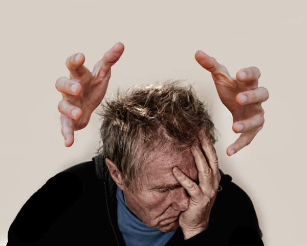 Stressed-out man with hands closing in on him