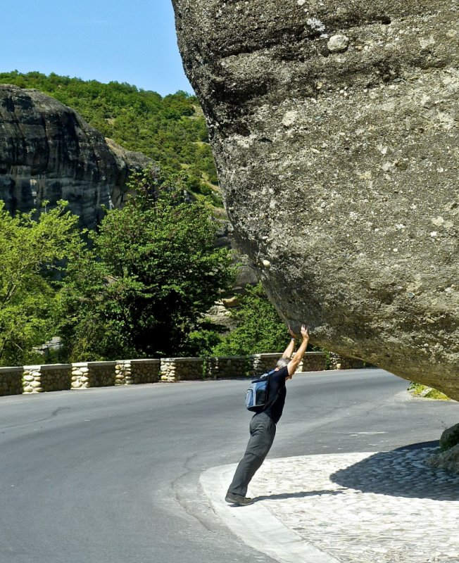 Man trying to hold up a huge boulder